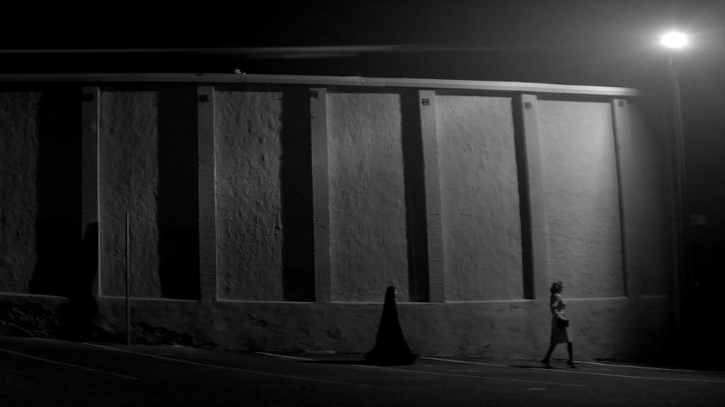 A wide shot of The Girl following a woman down the street.