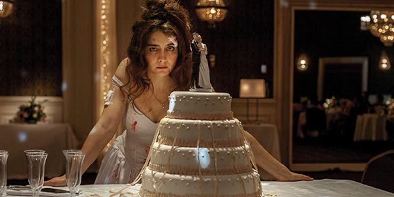A woman in a wedding dress stares at a wedding cake. She has a bandage over one eye and her dress is stained with blood.