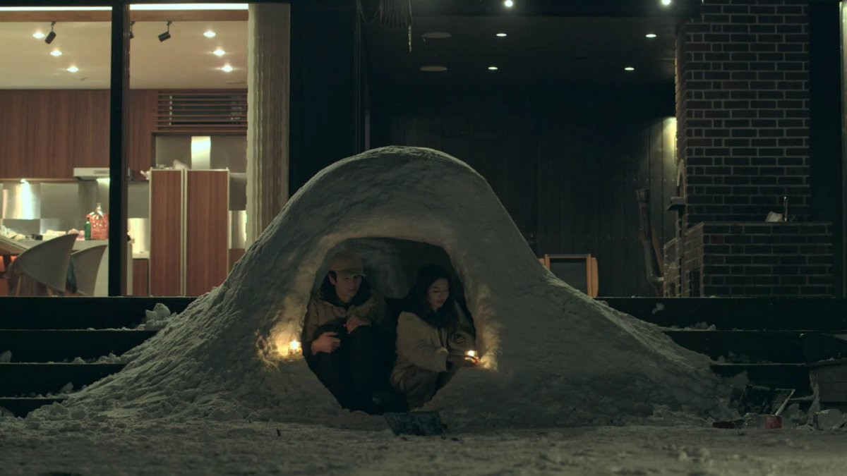 A man and a woman sit in an igloo in the front yard of Terrace House.