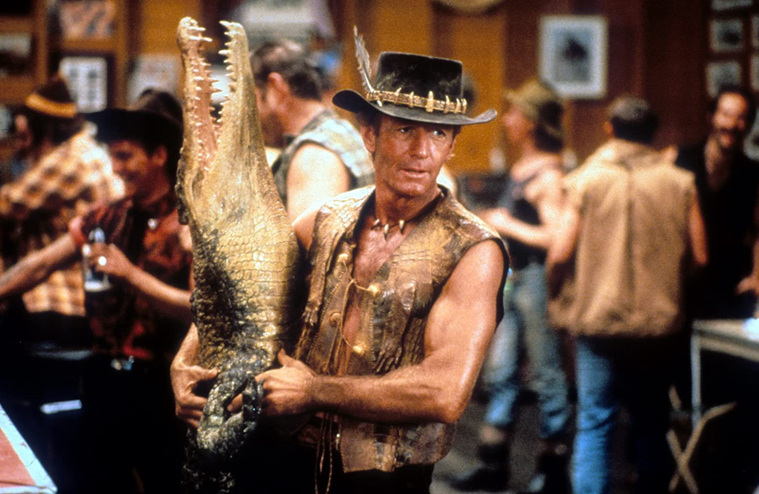 Mick, wearing an open leather vest and a feathered hat, holds a taxidermy crocodile