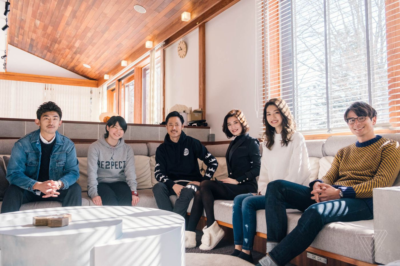 Six young adults sit in a spacious living room, smiling at the camera.