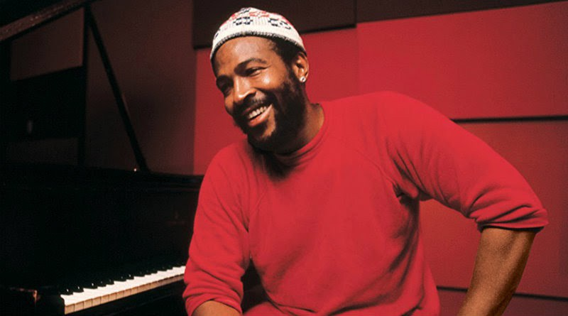 Marvin Gaye sits in front of a piano. He wears a beanie, a red sweater, and a bright smile.