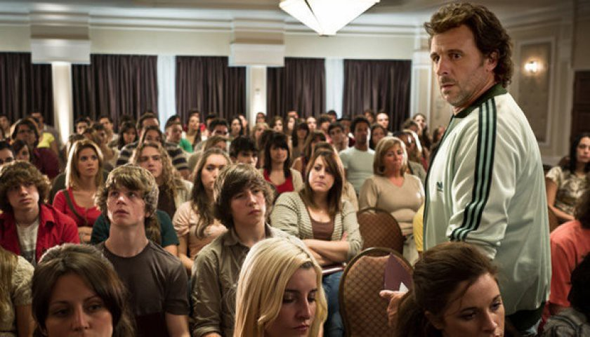David stands in front of a room full of seated teenagers