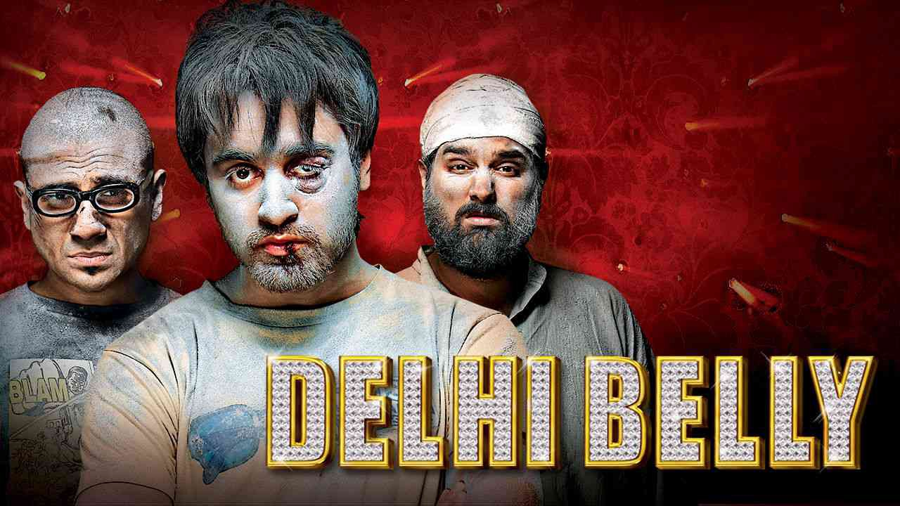 A poster for Delhi Belly. The three leads appear beaten up and covered in dust. The man in the center has a black eye and a split lip.