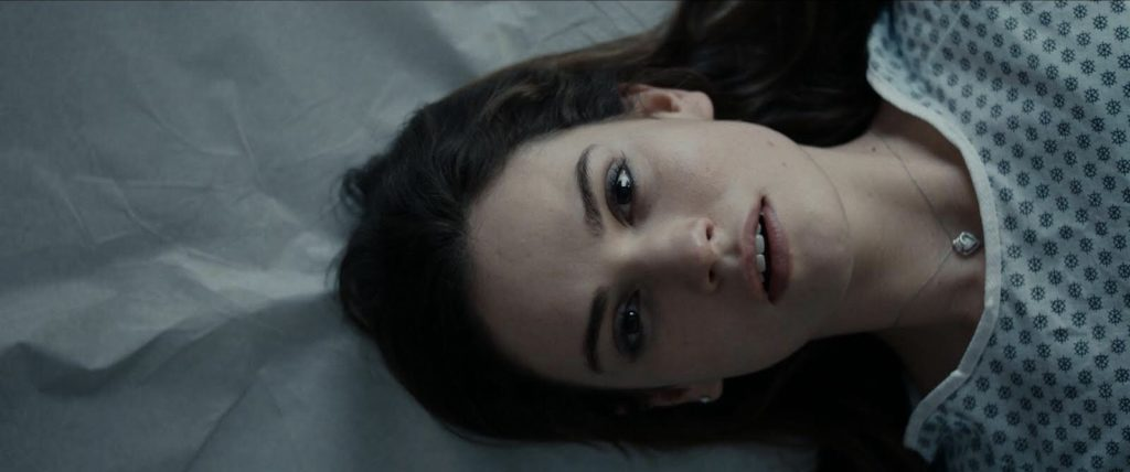 Deb (Lily James) wears a hospital smock and lies on an examination table.