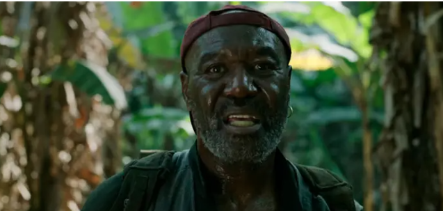 Paul stands in the jungle. He's an aging Black man wearing a backwards baseball cap.