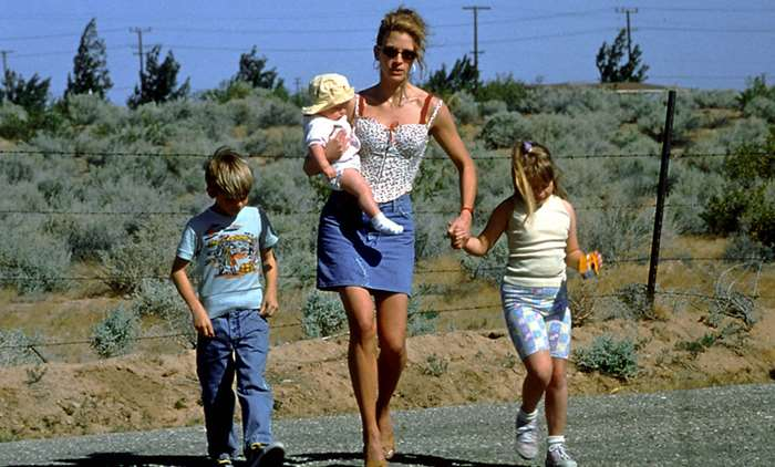 Erin, in one of her many iconic outfits, taking her kids to work with her