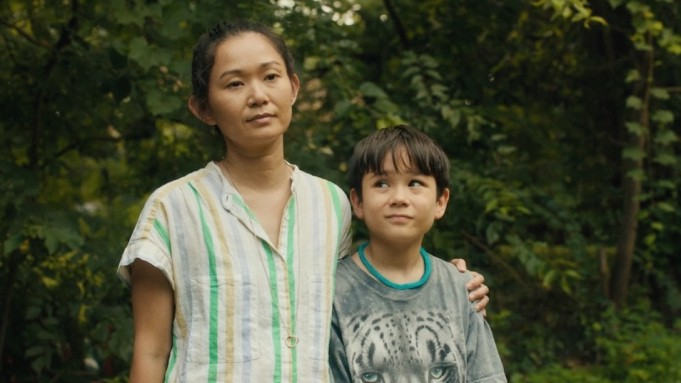 Kathy, a middle aged Asian woman, stands outdoors with her young son, Cody. She has her arm around his shoulder.