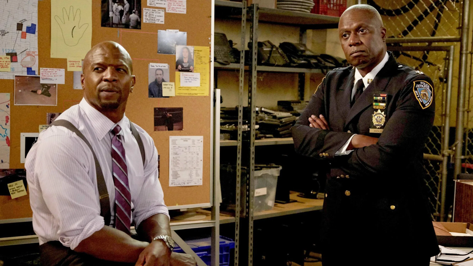 Terry and Holt, two Black police officers, in front of an evidence-filled cork board.