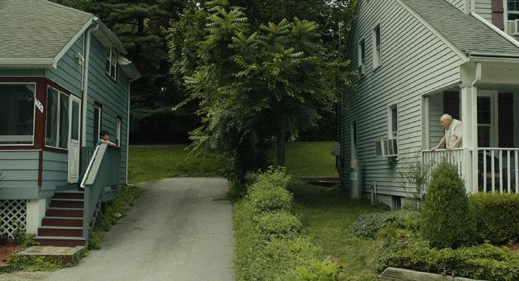 Two pale blue houses stand across from each, divided by a driveway and a lush green law. Del stands on one of the house's porch.