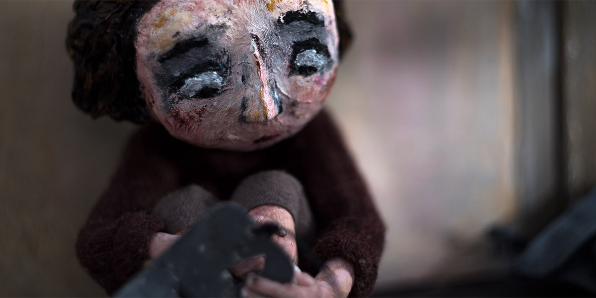 A paper mache doll of a young girl sits with her arms wrapped around her legs.