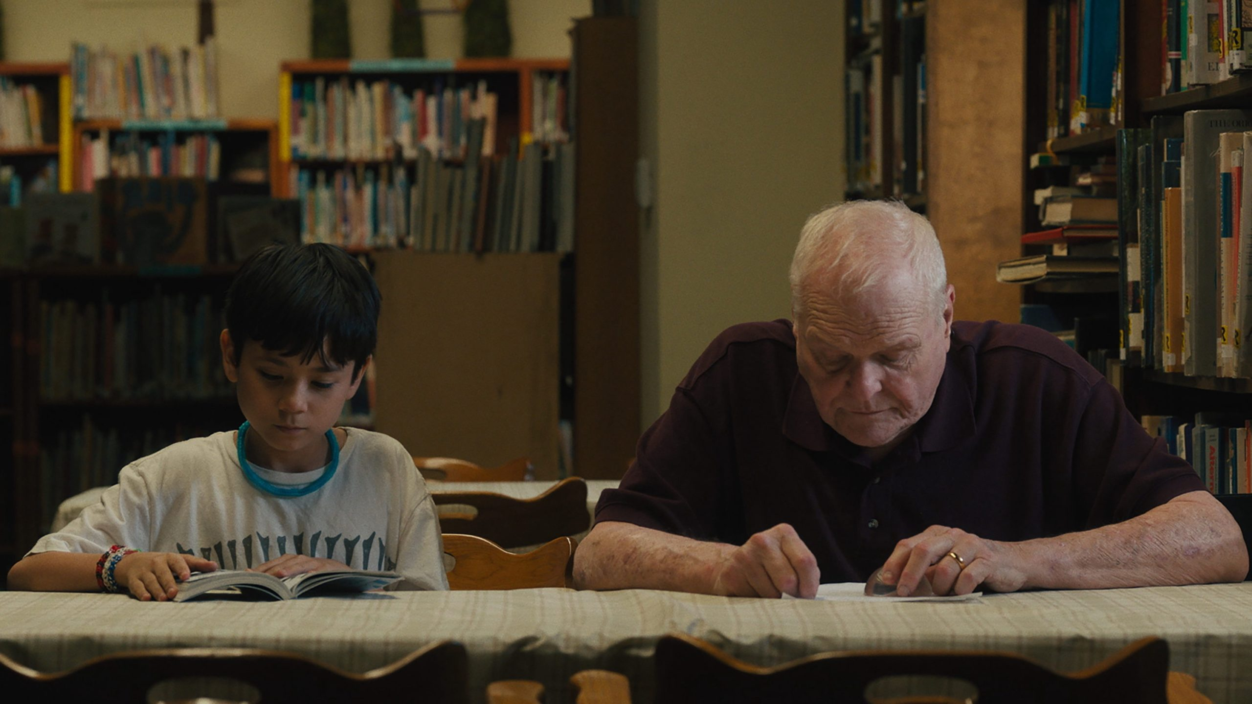 Cody and Del (an elderly white man) read together at a table.