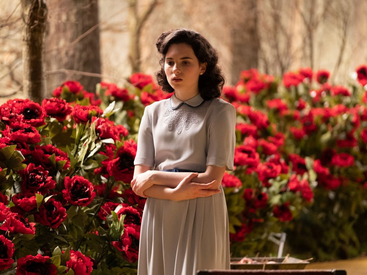 Darci Shaw as young Judy. She stands in front of a rose bush, arms crossed and looking slightly distraught.