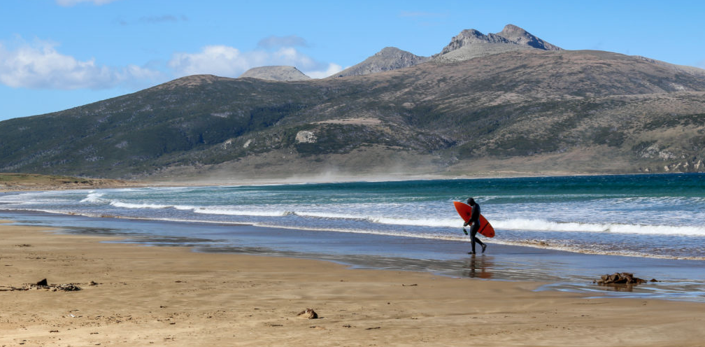 A surfer with a board under their arm walks along Argetina's Patagonian Coast