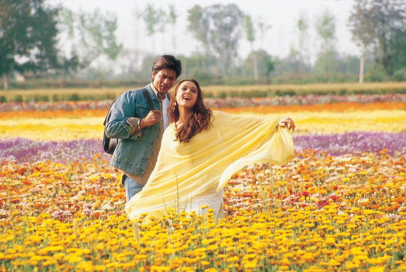 Veer (Shah Rukh Khan) and Zaara (Preity Zinta) stand in a field of yellow and pink flowers