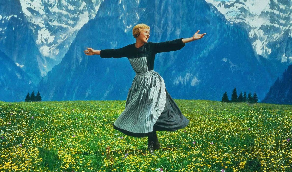 Maria (Julie Andrews) spins in a field in front of the Alps
