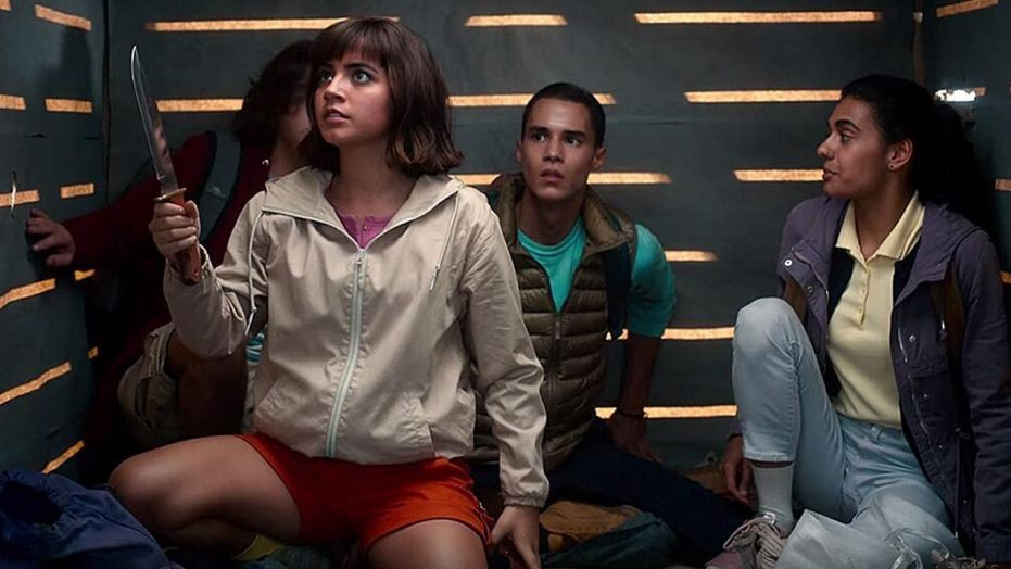 Dora, Randy (Nicholas Coombe), Diego, and Sammy are trapped in a crate. Dora wields a knife.
