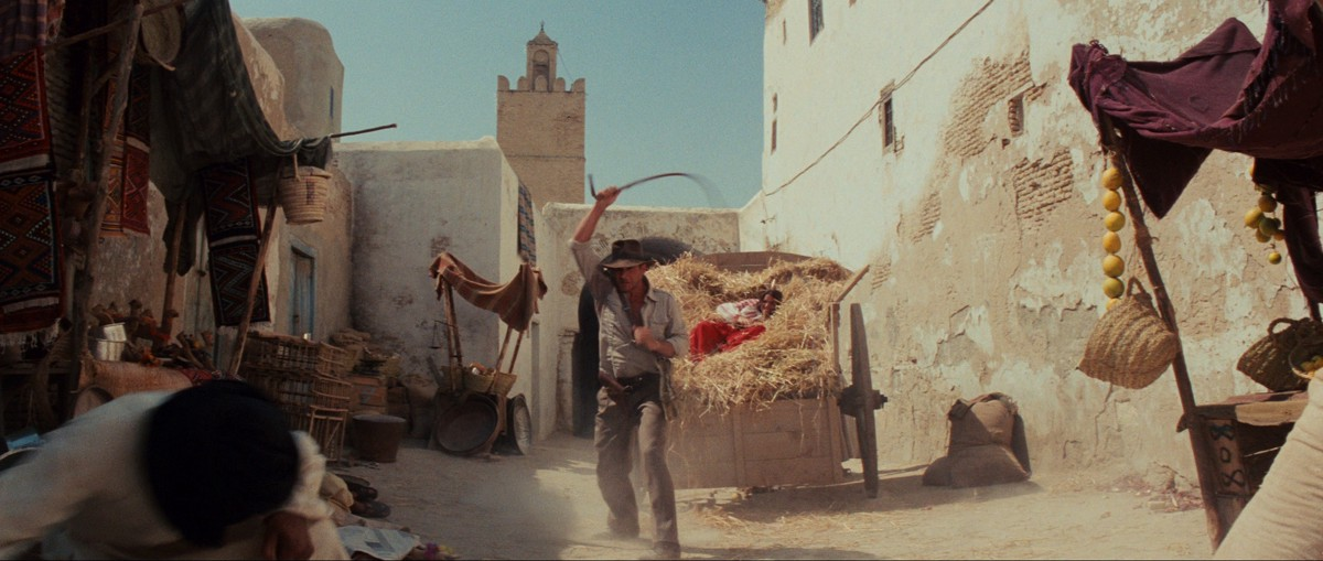 Indiana Jones cracks his whip in a marketplace