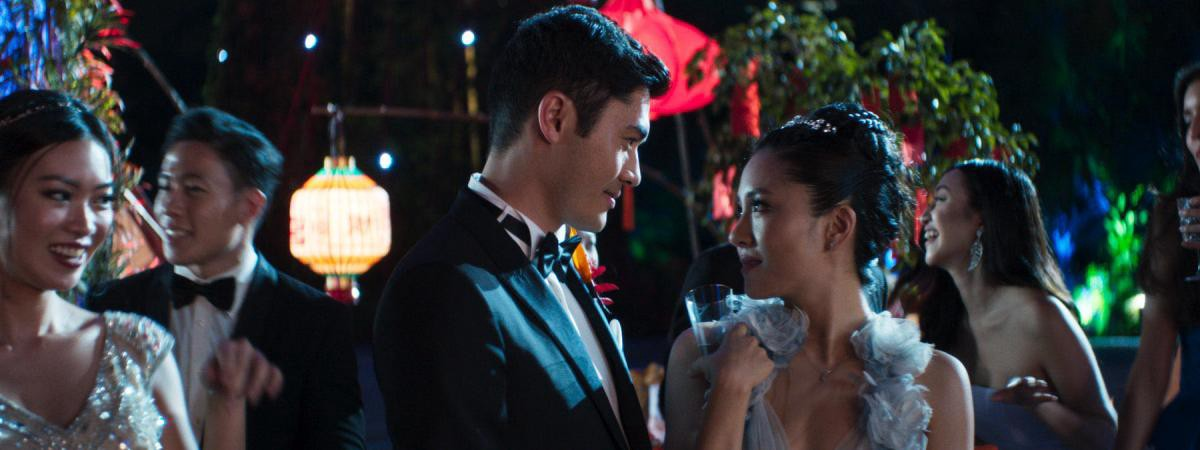 Nick (Henry Golding) and Rachel (Constance Wu) smile fondly at each other. They are dressed in evening wear and attending an outdoor party.