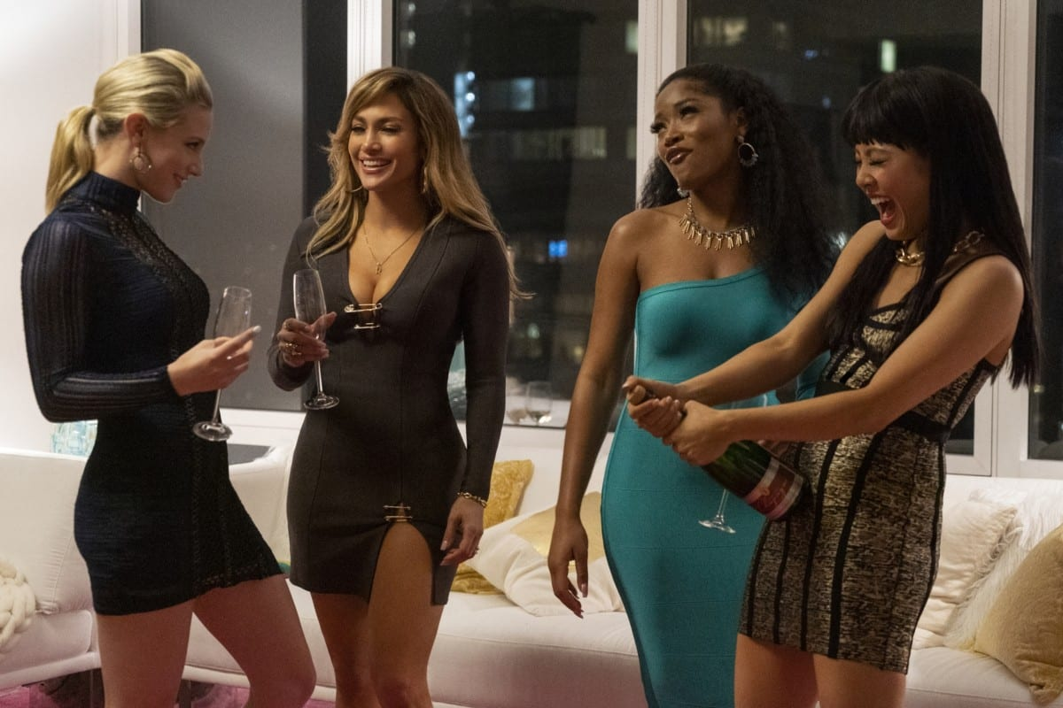 Four women in evening wear celebrate with a bottle of champagne.