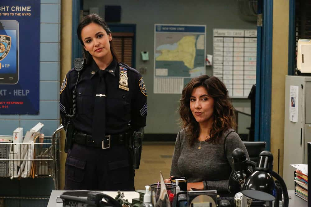 On the left, Melissa Fumero as Amy. She's standing and wearing a police uniform. Rosa, played by Stephanie Beatriz, sits to her right wearing civilian clothing.