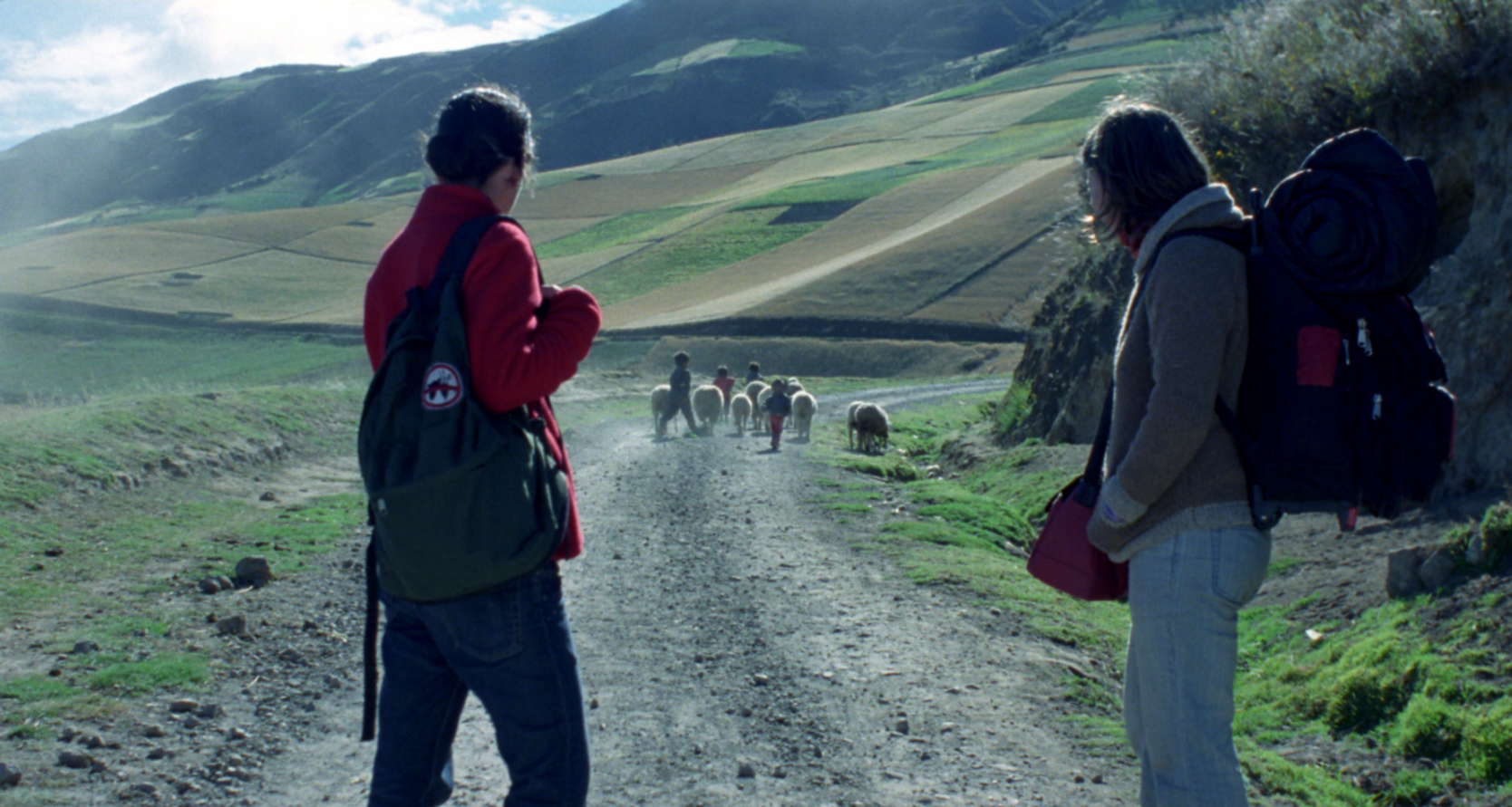 Two hikers observe a small herd of sheep and several children walking down a dusty road