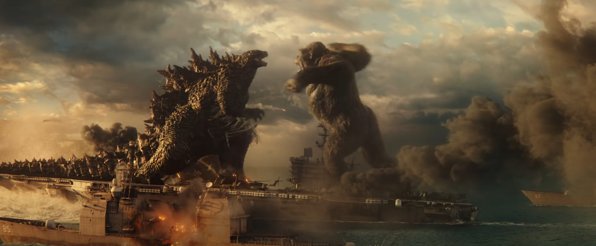 Godzilla and Kong face off on the back of an aircraft carrier. Kong is about to punch Godzilla in the face.