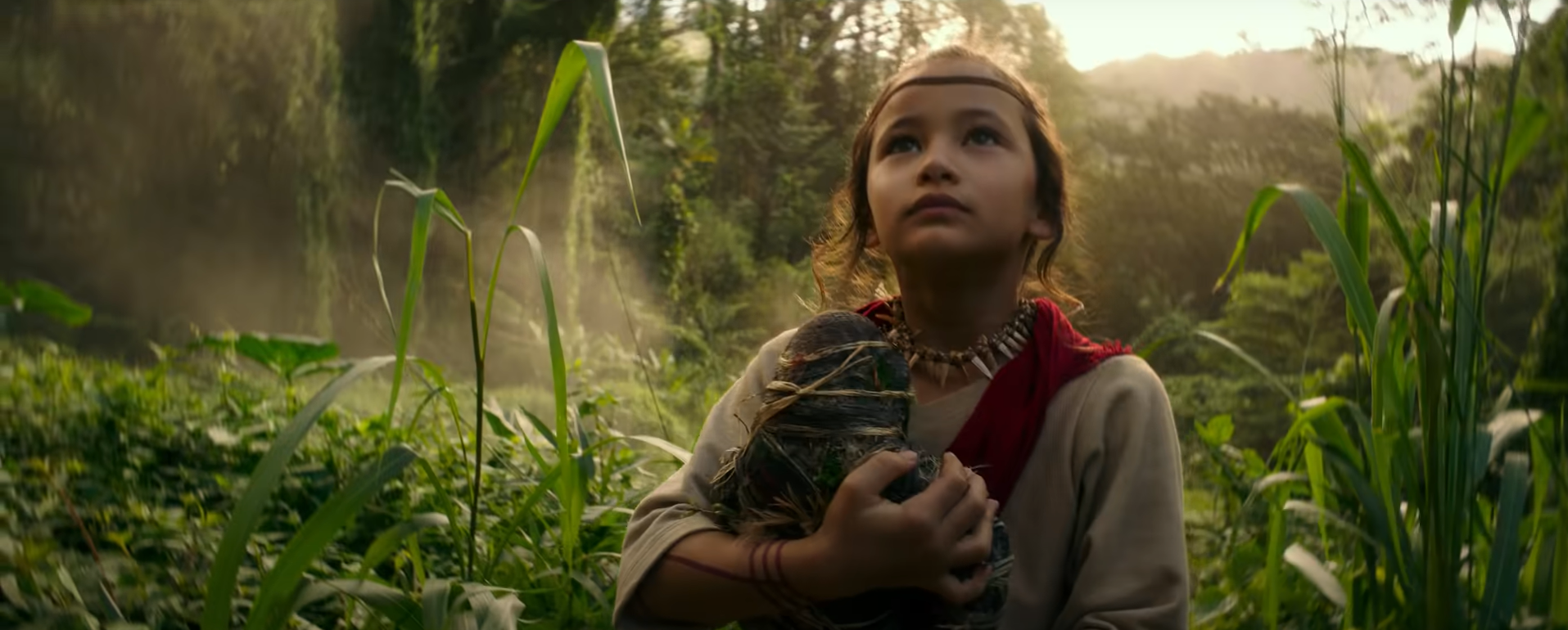 Jia (Kaylee Hottle), a young Indigenous girl holding a homemade Kong doll, stands in a jungle.