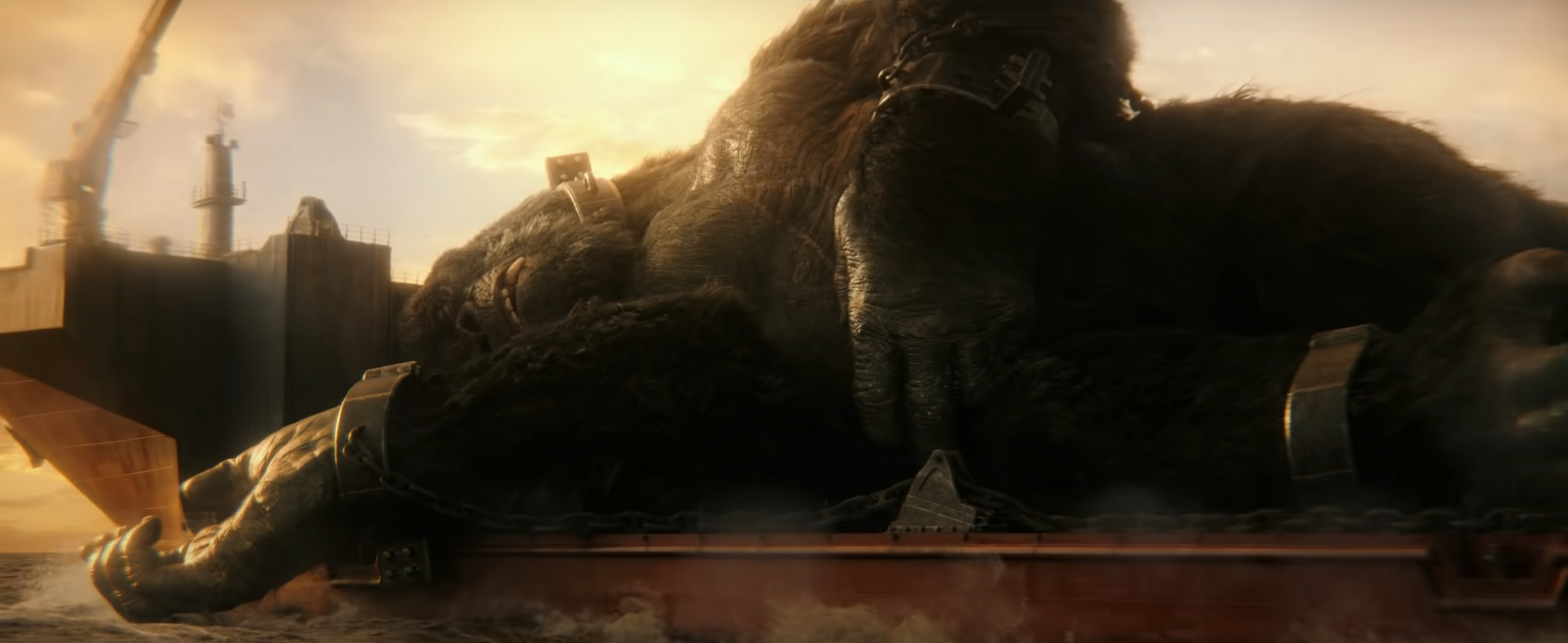 King Kong sleeps on the back of an aircraft carrier, held down by manacles.