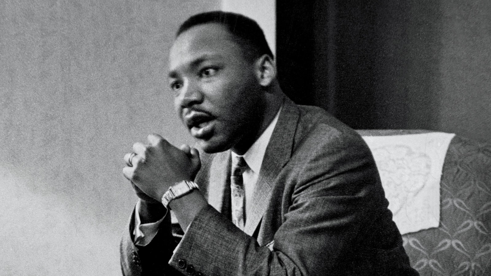 A black and white photo of Dr. Martin Luther King Jr. He is seated with his hands clasped in front of him, talking to someone to the left of the frame.