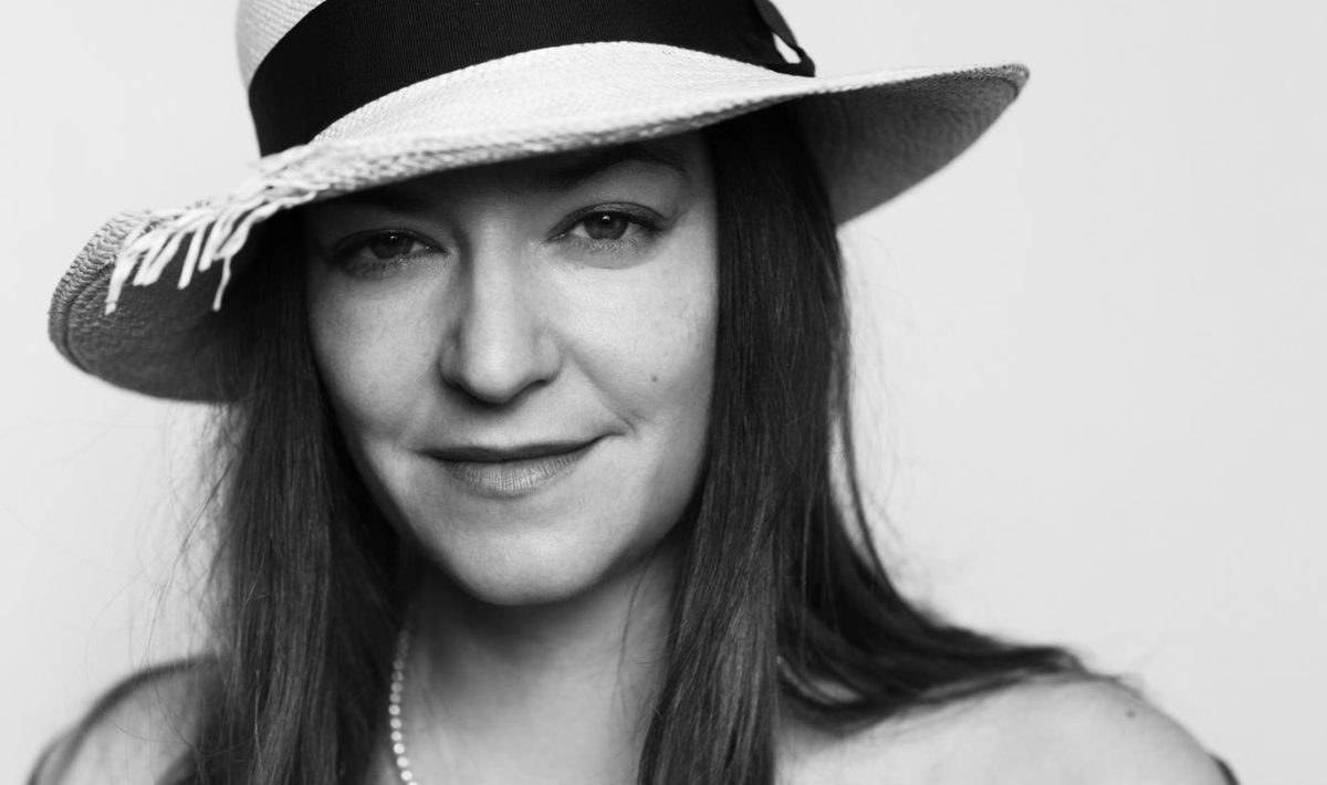 A black and white shoulders-up shot of Lynne Ramsay. She wears a wide brimmed hat, a pearl necklace, and a slight smile.