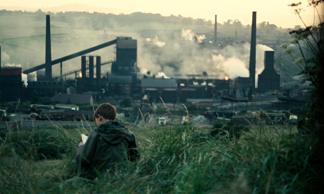 A young boy in a raincoat sits in a grassy field overlooking a factory