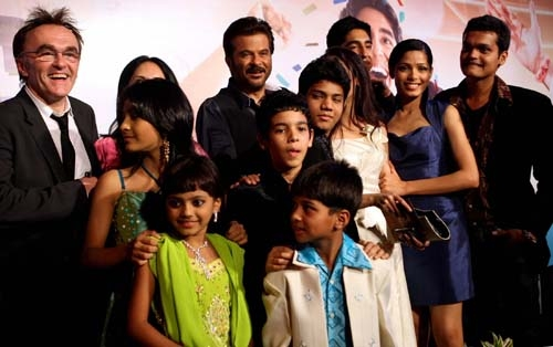 The cast of Slumdog Millionaire (who are all Indian) posing on the red carpet with the film's director Danny Boyle (who is white).
