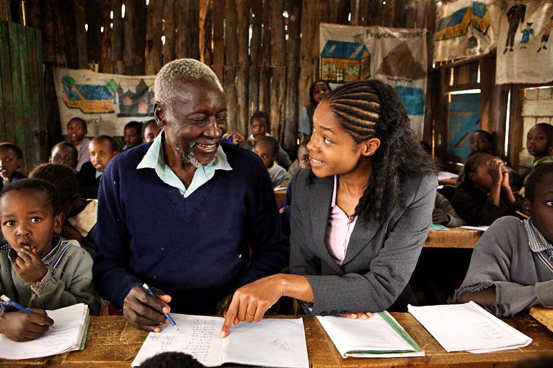 An elderly Kenyan man sits in a classroom full of young children. He's taking notes and sharing a smile with a teacher, a young Kenyan woman.