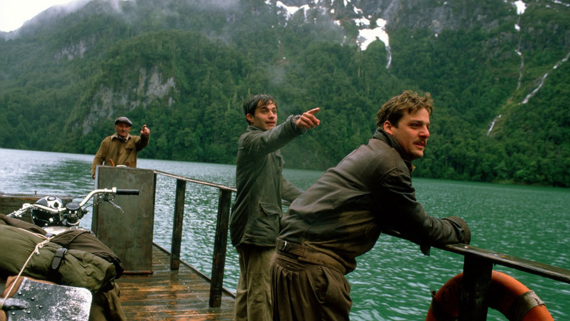 Three men ride down the river on a ferry. Two of the men are pointing to the right of the frame.