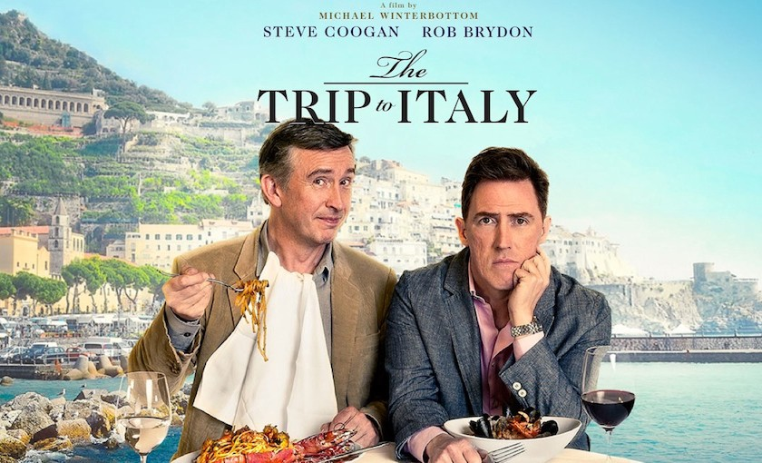 A promotional poster for The Trip to Italy. Steve Coogan and Rob Brydon eat an Italian meal with a beautiful island town in the background.