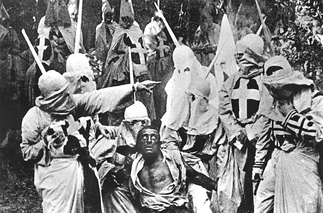 A screenshot from Birth of a Nation. A Black character (played by a white actor in blackface) is captured by hooded Klansmen.
