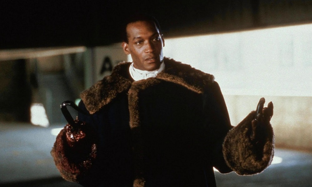 Tony Todd as Candyman. He's a young Black man with a hook in place of a right hand. He wears a brown fur coat.