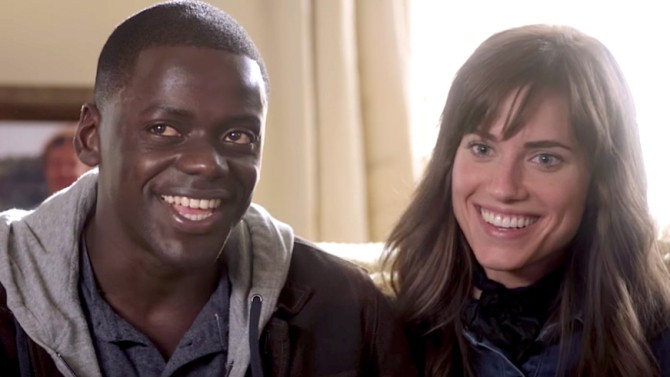 Chris and Rose (Daniel Kaluuya and Allison Williams) sit close together on a couch, smiling.