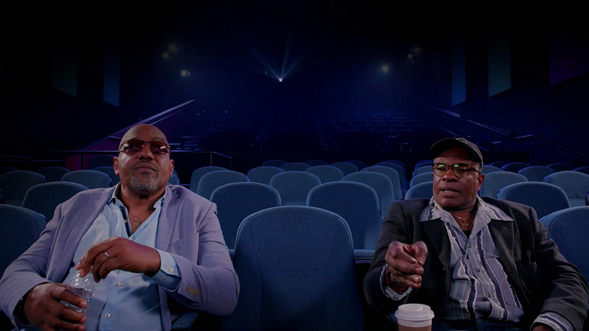 Keith David and Ken Foree (both Black men and prominent actors from horror films) sit in a movie theatre