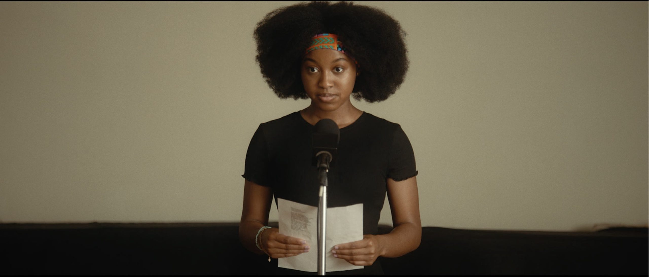 Kai stands in front of a microphone, holding a sheet of paper. She wears a black T-shirt and a headband, and wears her hair as an afro.