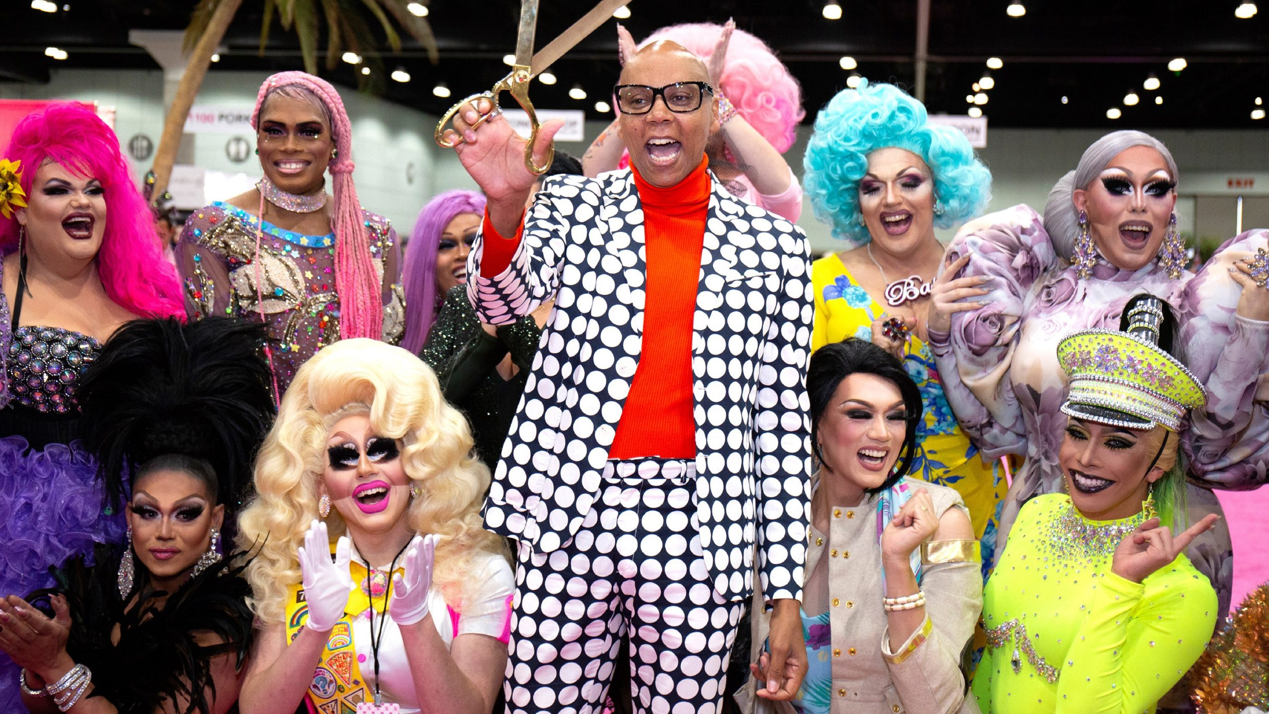 Rupaul, out of drag in a checkered suit, holding a pair of a golden scissors. A crowd of drag queens cheer behind her, including Trixie.