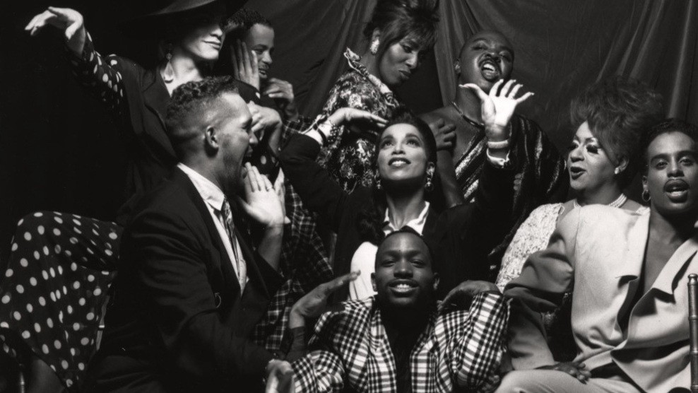 A black and white photo of a group of drag and ball performers. Some pose for the camera, and others laugh and smile at each other.