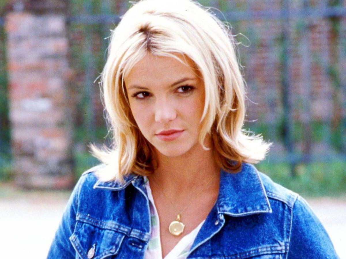 """Still of Britney Spears as Lucy in """"Crossroads"""". She is wearing a gold necklace and blue jean jacket."""