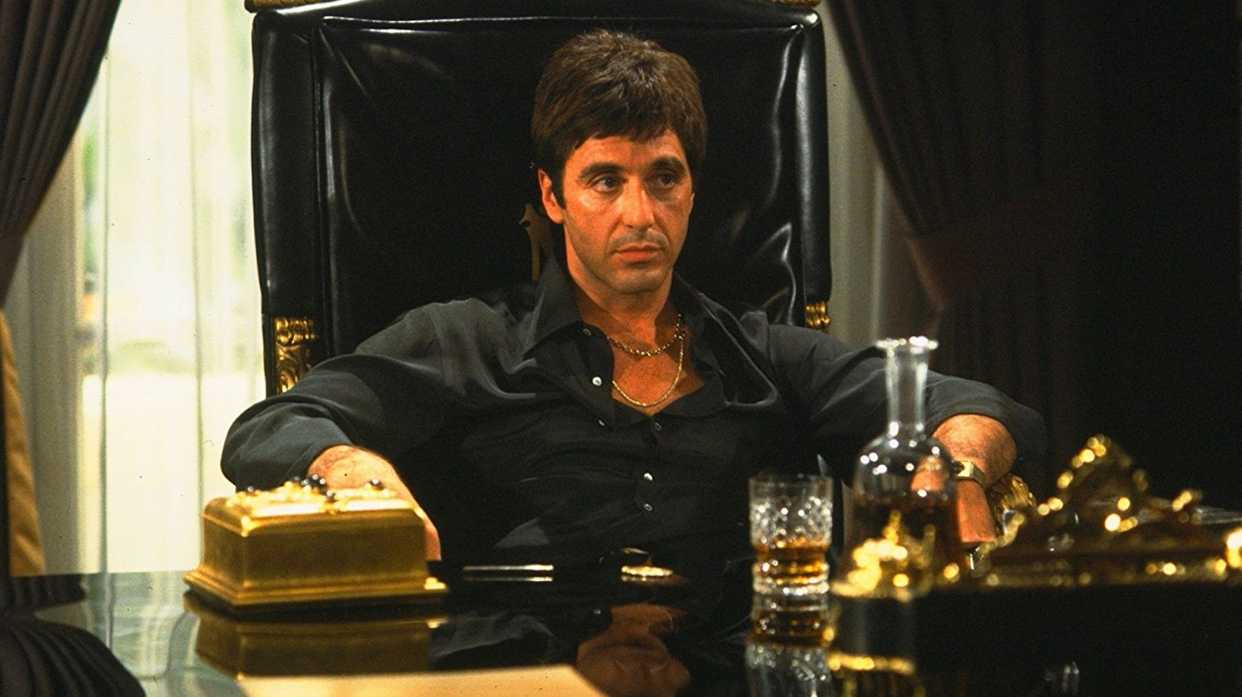 Al Pacino sits at a desk with a drink in front of him.