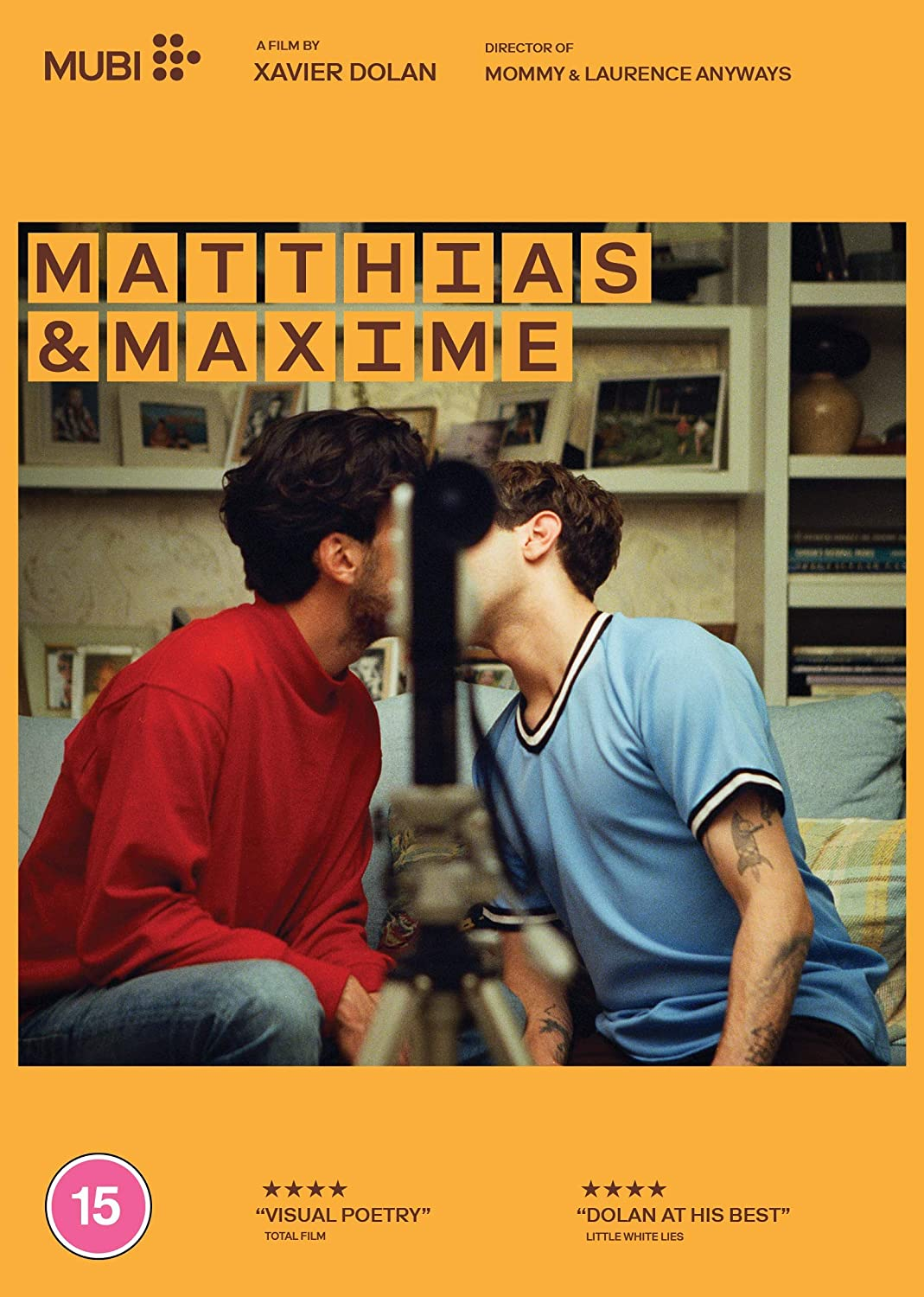 Poster for Matthias & Maxime. The pair kiss with a camera blocking their face.