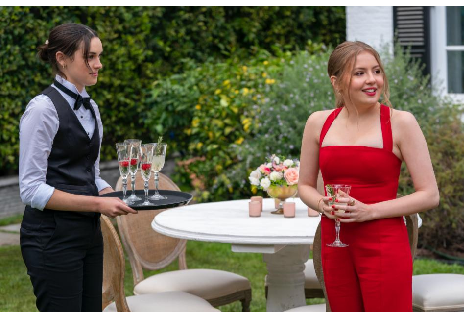 A still of Lake and Lucy standing together at Mia's dad's wedding