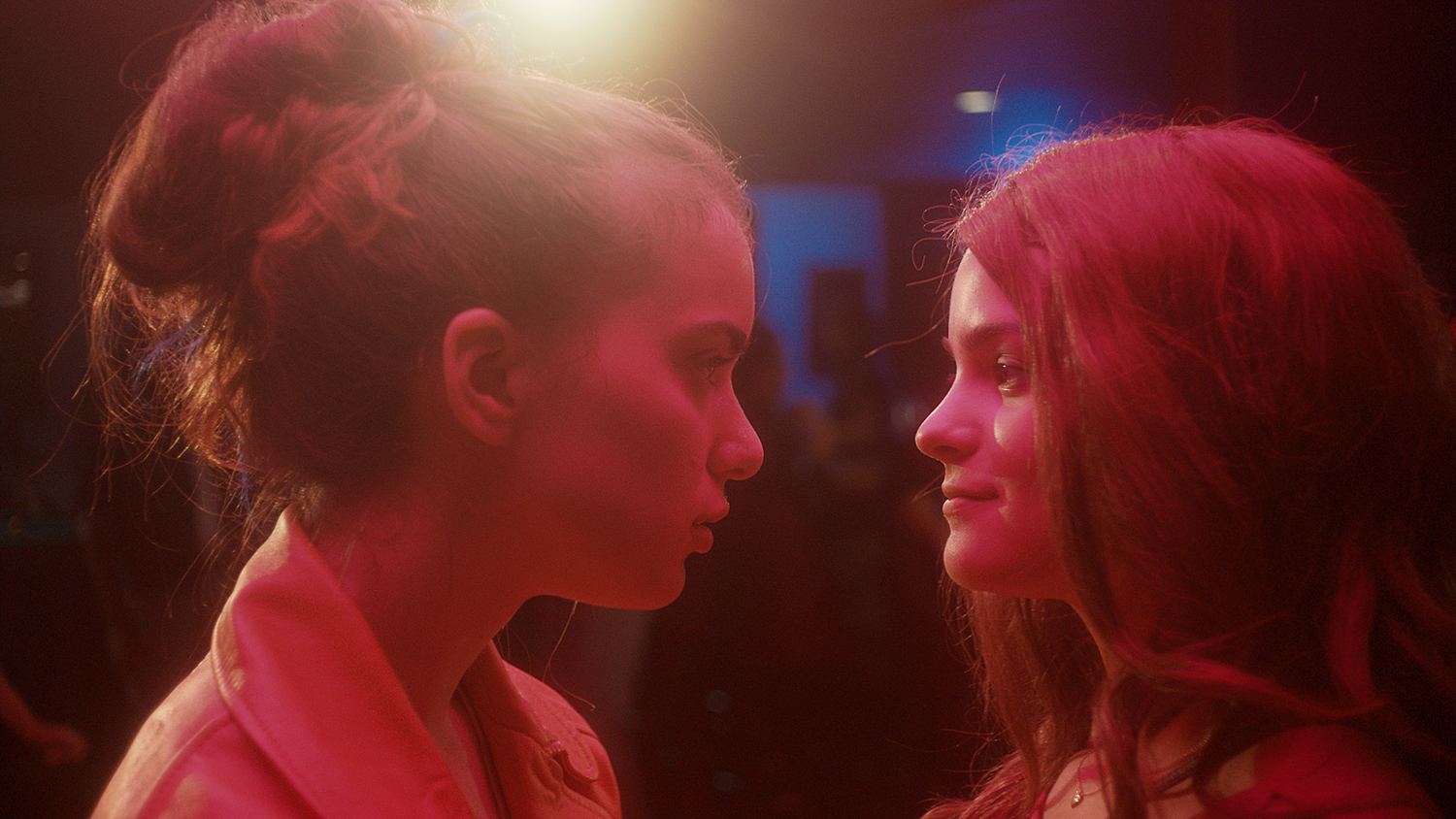 Anne and Sasha stare at one another in a club setting with pink lighting