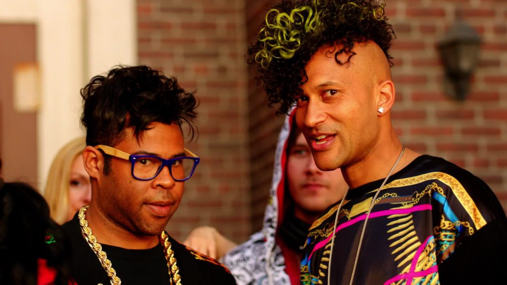 """A still from Key & Peele's """"Nooice"""" sketch, with the two standing shoulder-to-shoulder in a small crowd. Peele wears blue and yellow hipster glasses and a thick gold chain and has an uncomfortable expression on his face. Key has a curly yellow-streaked mohawk, wears a brightly colored shirt, and is smiling."""