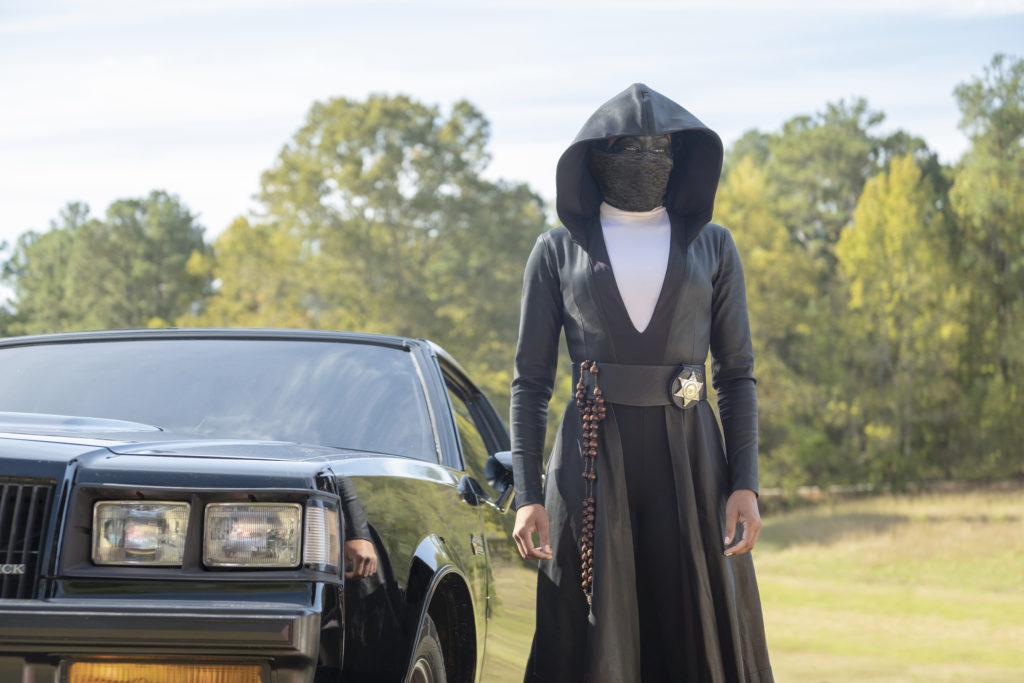 Regina King as Angela Abar in Watchmen. She stands in front of a black car, wearing a long black cloak with a sheriff's badge on the waist and a black mask that entirely covers her face.